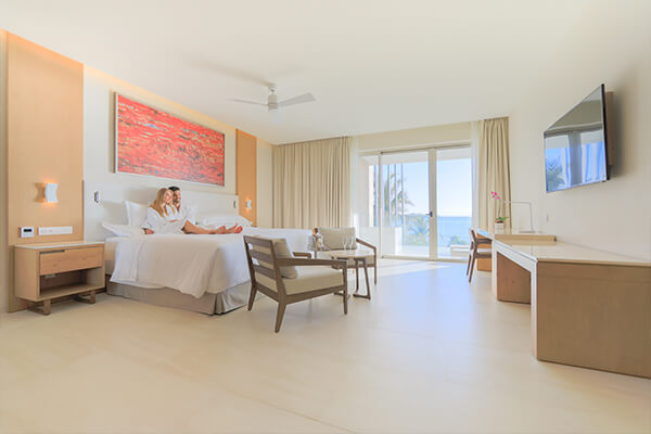 Luxurious suite with elegant décor and breathtaking ocean views from the balcony.